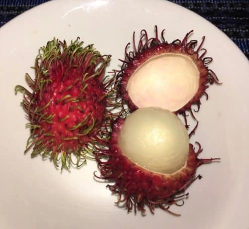 Rambutan: one with the skin and one cut open to reveal the fruit